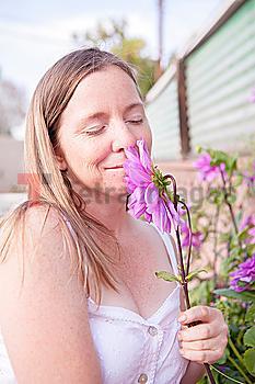 Mixed race woman smelling flowers in garden