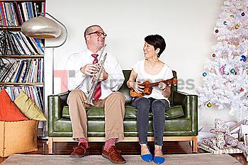 Couple playing music near Christmas tree