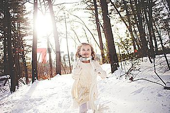 Caucasian girl running in snowy forest