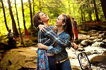 Girls hugging in forest creek