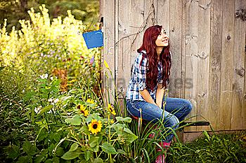 Gardener sitting near wooden shed in backyard