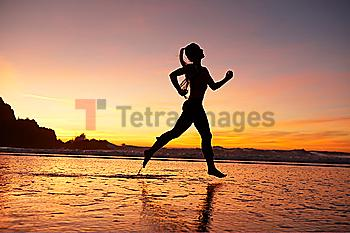 Silhouette of woman running on beach at sunset