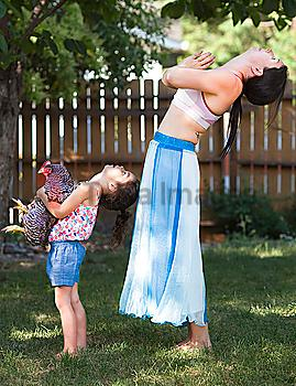 Mother and daughter practicing yoga with chicken in backyard