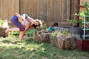 Mother and daughter practicing yoga in backyard