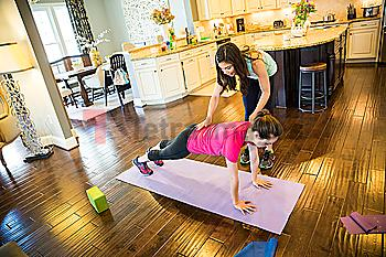Woman exercising with trainer in home