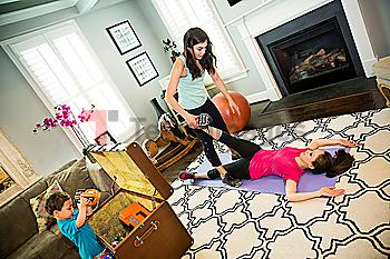 Mother exercising with trainer in home