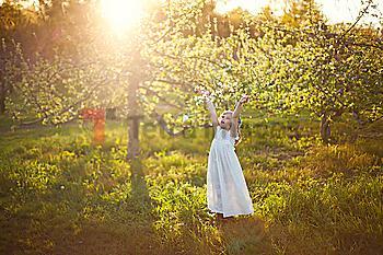 Caucasian girl tossing flower petals outdoors