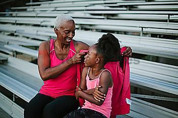 Grandmother wrapping sweater around granddaughter on bleachers