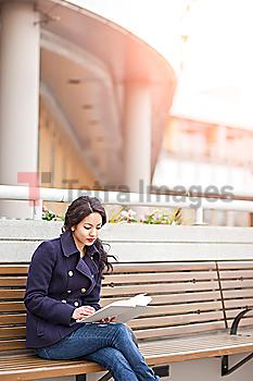 Mixed race woman sitting on bench reading