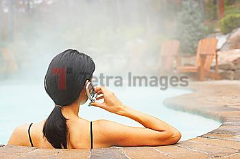Woman talking on cell phone in hot tub