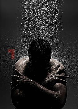 Caucasian man sitting in shower
