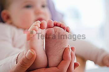 Close up of mother´s hand holding baby daughter´s (6-11 months) feet