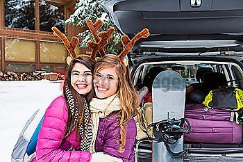 Women posing near car in winter wearing toy antlers