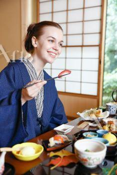 Caucasian woman wearing yukata eating at traditional ryokan, Tokyo, Japan