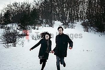 Caucasian couple running from forest in winter