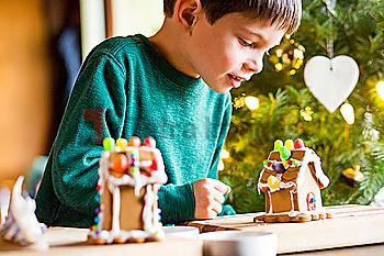 Mixed race boy building gingerbread house