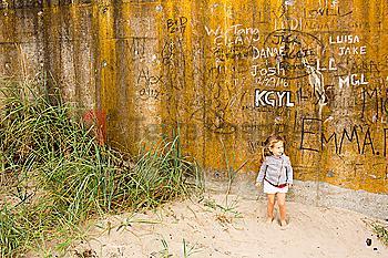 Caucasian girl standing in sand near graffiti wall