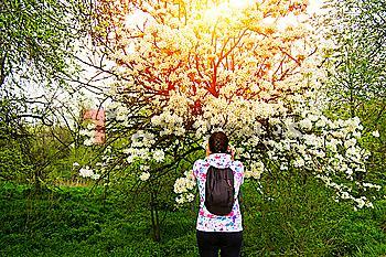Caucasian woman smelling flowers on tree