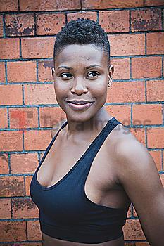 Black athlete smiling near brick wall