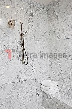 Shower head on marble bathroom wall at home