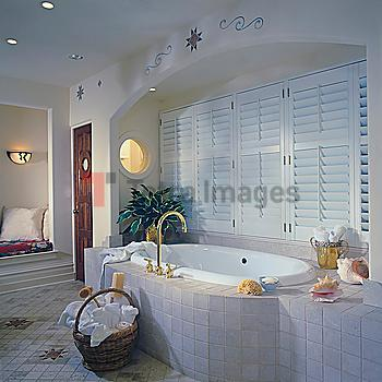 Tub with tile surround set in arched alcove with shuttered windows, round window. Basket of towels on tile floor, southwest designs, round window,