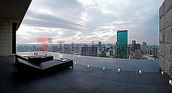 Two lounge chairs on outdoor terrace overlooking city