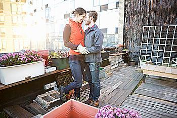 Couple hugging in urban rooftop garden