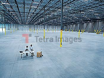 Architects using laptop and blueprint in empty warehouse