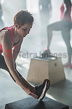 Athlete stretching leg in gym