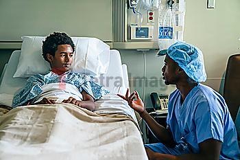 Black nurse talking to boy in hospital bed