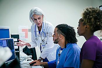 Doctor talking to nurses at computer