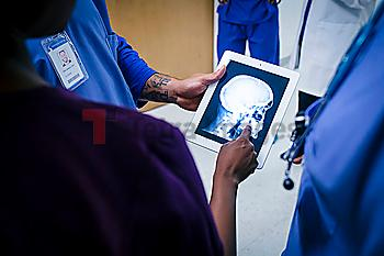 Doctors examining x-ray of skull and jaw on digital tablet