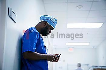 Black nurse leaning on wall texting on cell phone