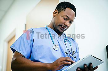 Black nurse using digital tablet in hospital
