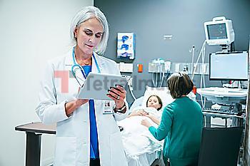 Caucasian doctor using digital tablet in hospital