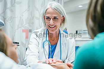 Caucasian doctor comforting girl in hospital bed