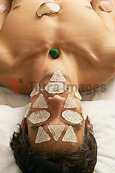 Hispanic man receiving stone and crystal spa treatment