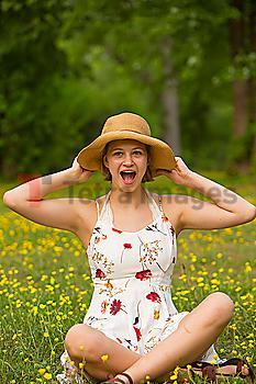 Surprised Caucasian teenage girl sitting in field of flowers