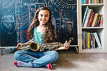 Mixed race girl holding saxophone on floor