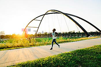Mixed race woman running on path in park
