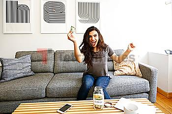 Mixed race woman celebrating with money for college