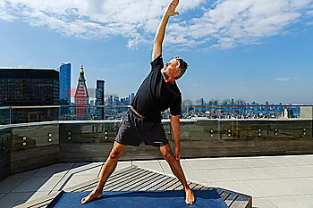 Caucasian man performing yoga on urban rooftop