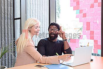 Creative business people using laptop at table