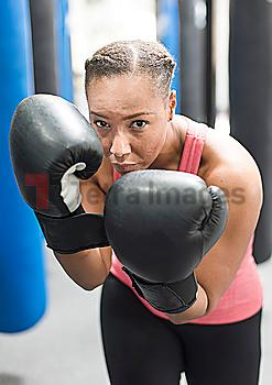 Portrait of Black woman wearing boxing gloves in gymnasium