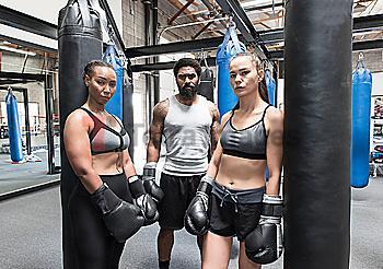 Man and women posing in gymnasium wearing boxing gloves
