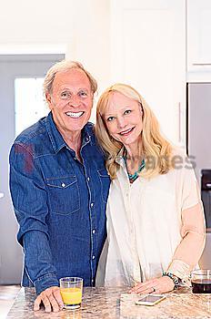Smiling Caucasian couple posing in kitchen