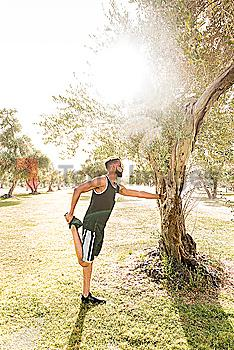 Black man leaning on tree in park stretching leg