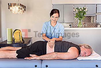 Physical therapist massaging back of man