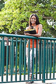 Black student using cell phone on walkway outdoors