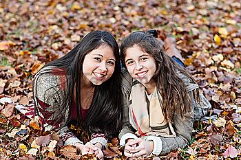 Hispanic sisters laying in autumn leaves